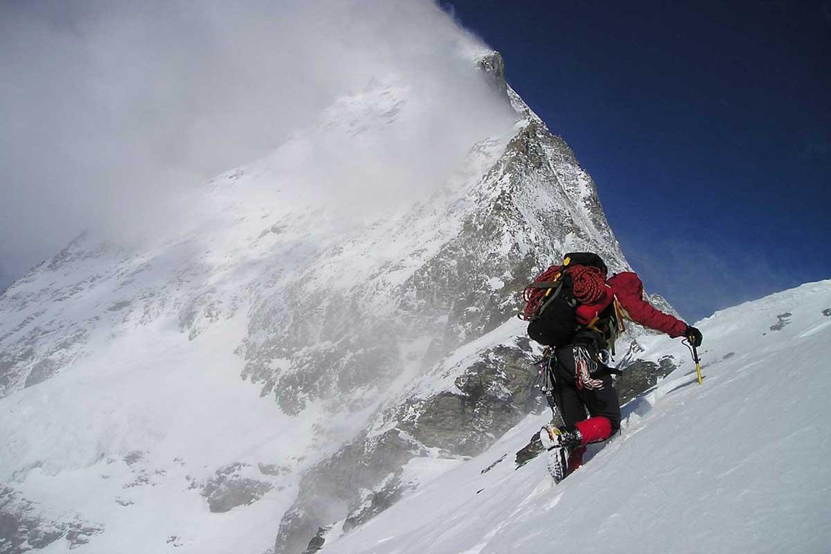 Alpinist climbing a snowy mountain