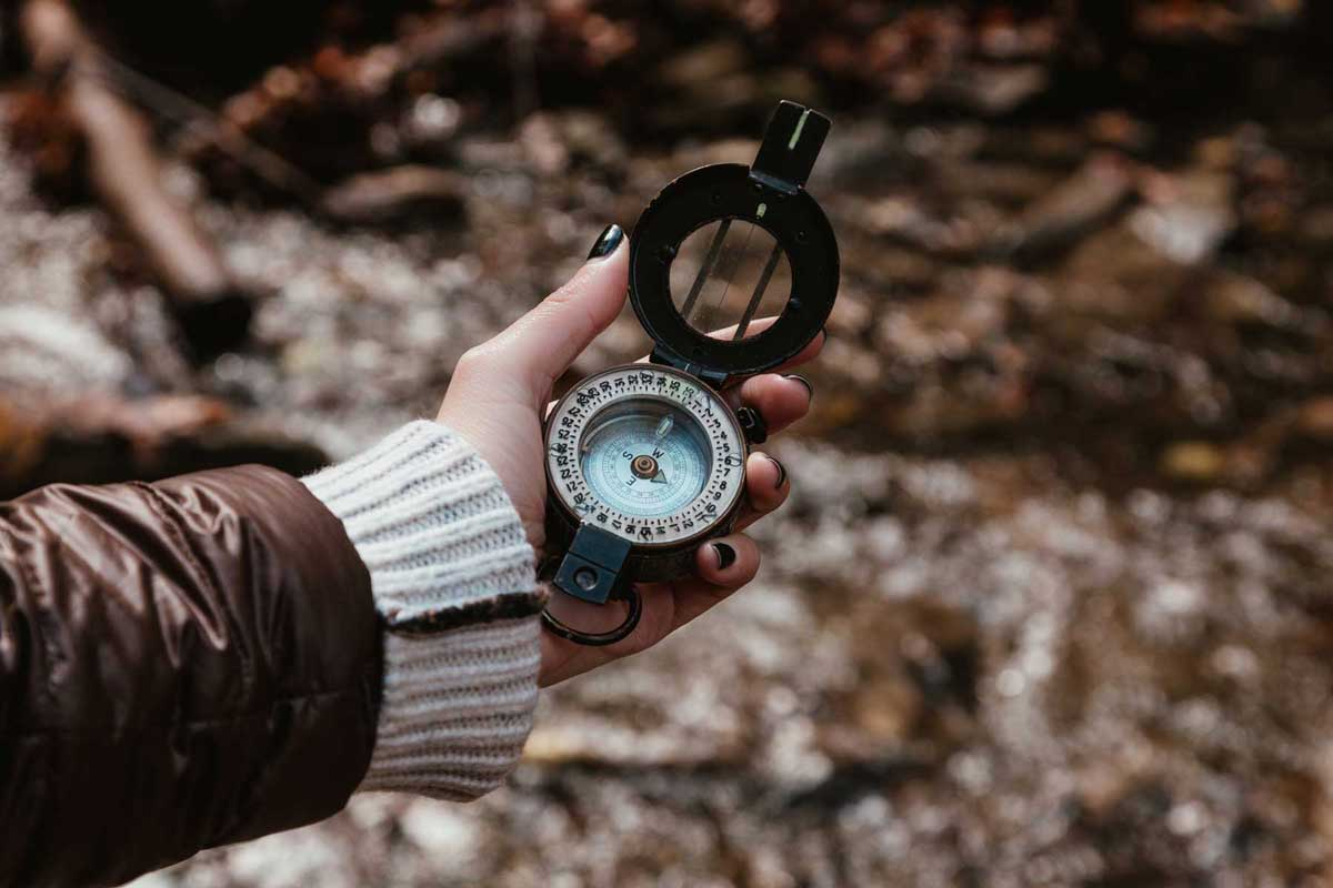 Checking compass on a hike in the woods