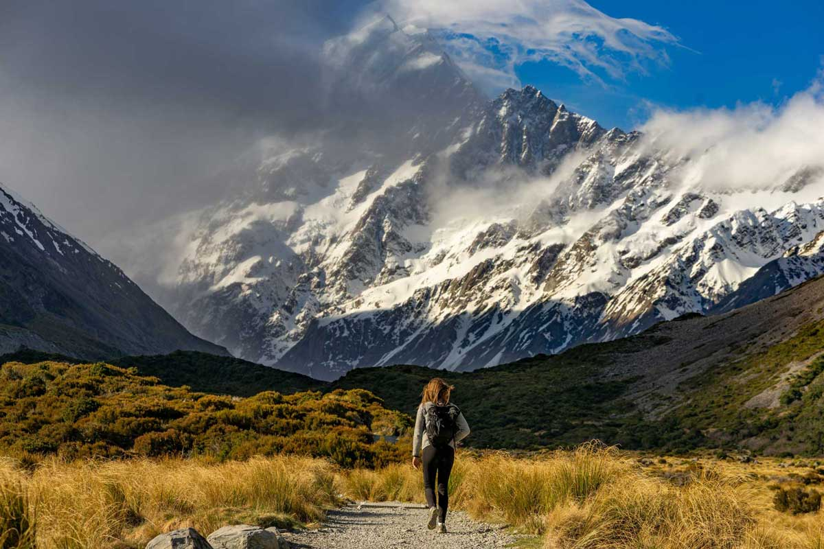 Hiker approaching snow capped mountains
