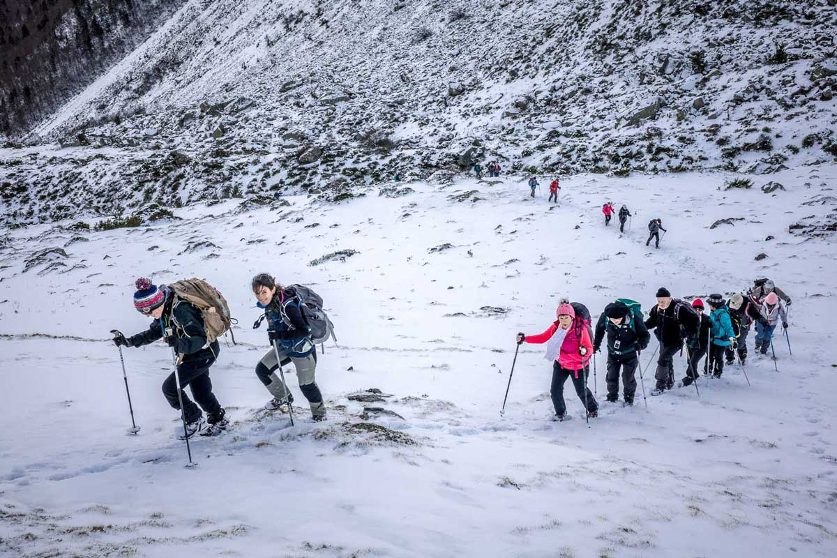 A group of hikers traversing snow-capped slope