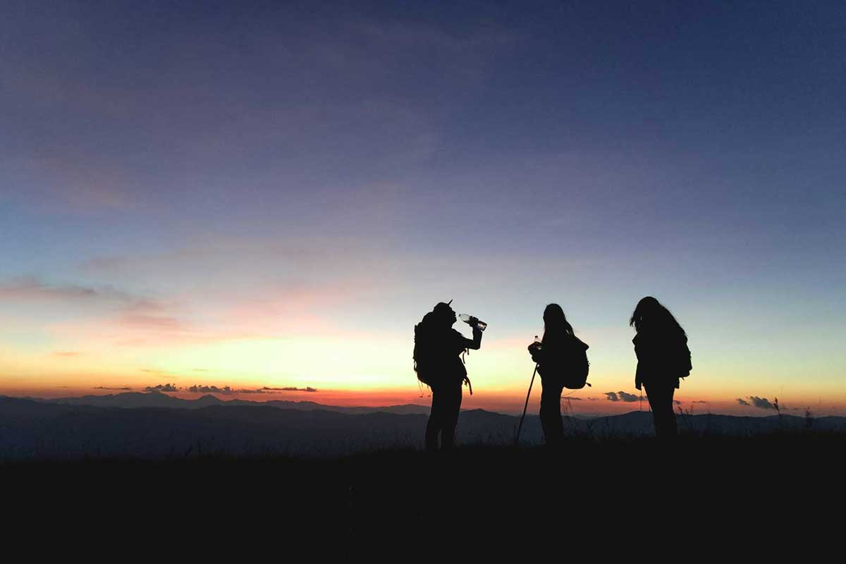 Three hikers talk on the trail