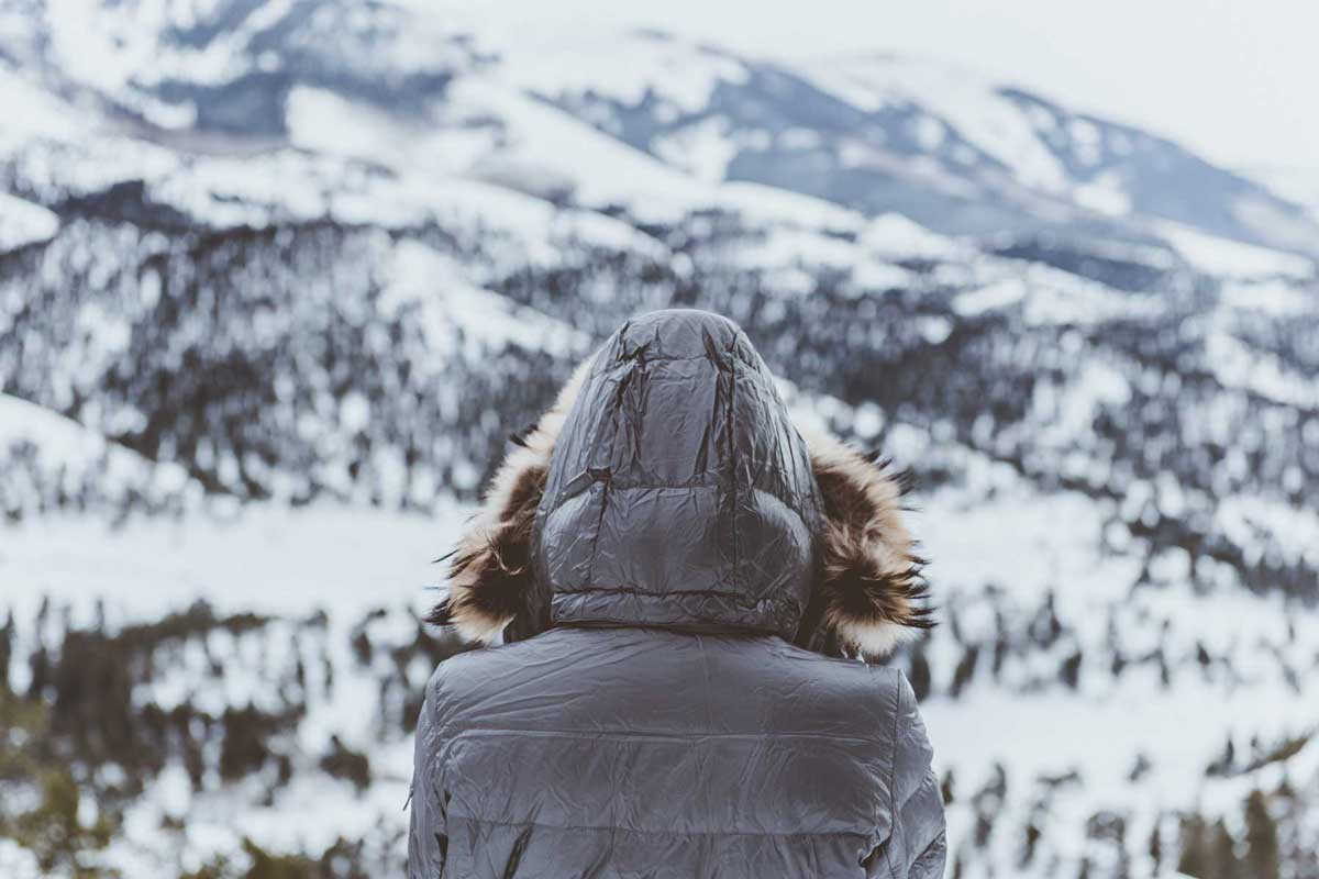 Hooded female hiker near snow landscape