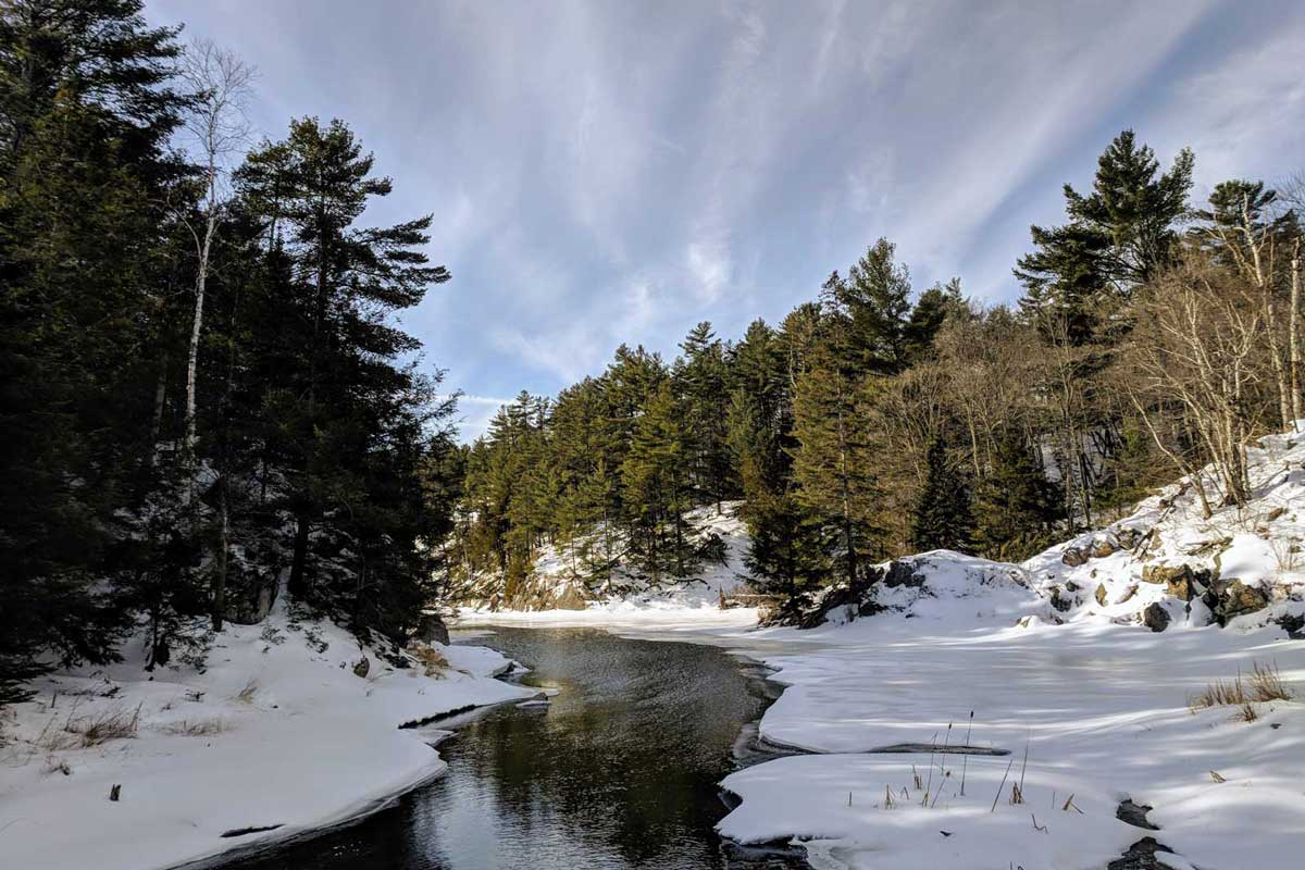 Stream through snowy winter shores
