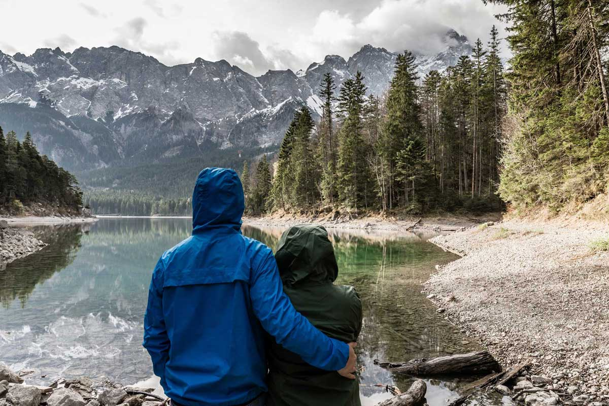 Two hikers with hooded jackets near lake