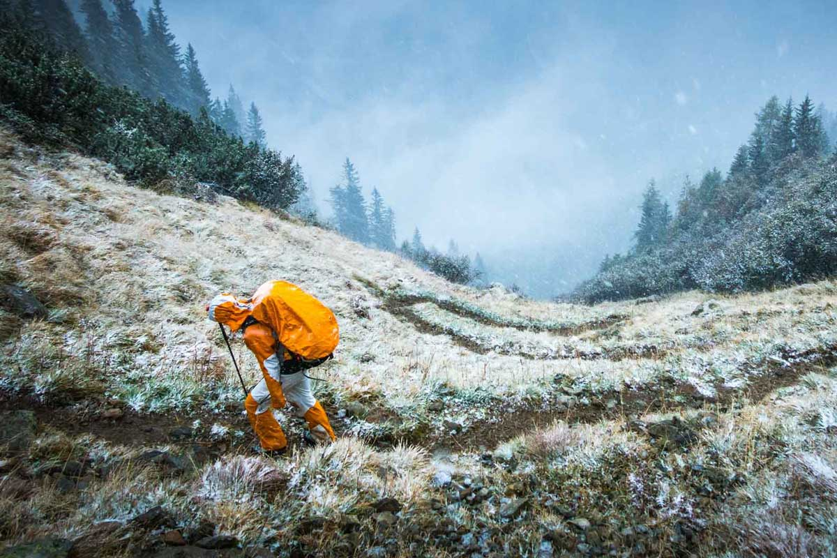Man wearing backpacking backpack with rain cover in snowy conditions