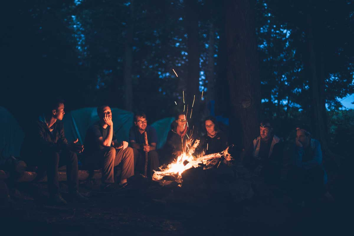 People sitting near campfire in bear country
