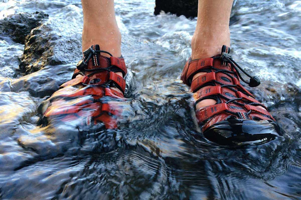 Hiker wearing hiking sandals is crossing a river