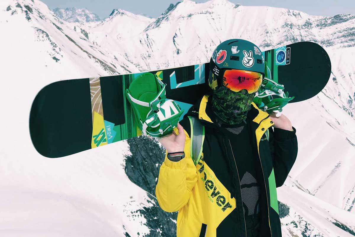 Man with neck gaiter, helmet, and snowboard