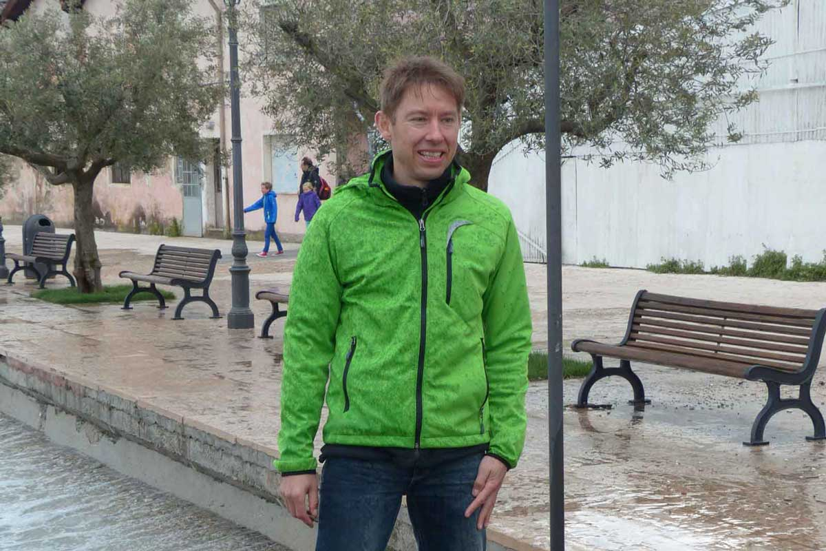 Man with green softshell jacket in town