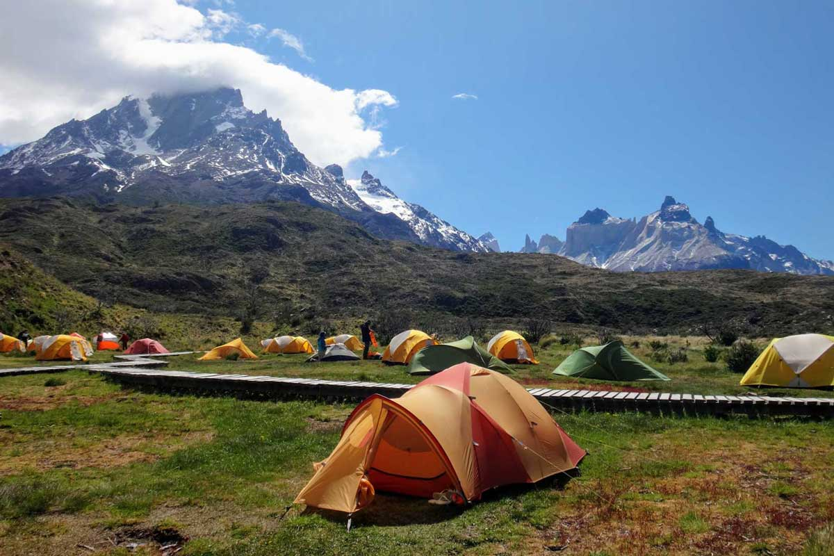 Tents surround boardwalk by mountains