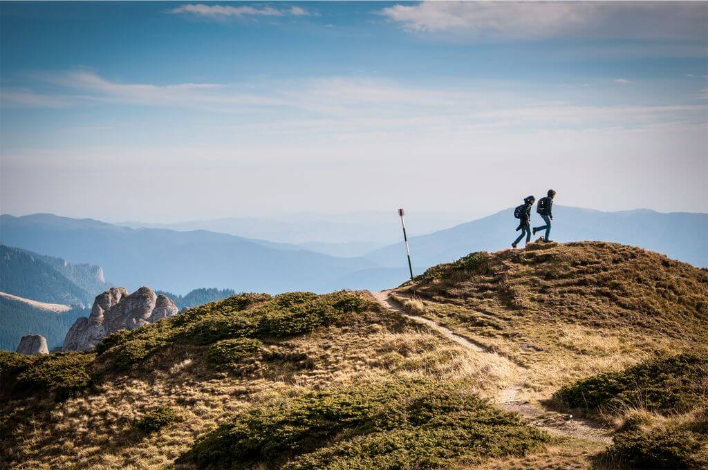 Two hikers traversing a hill