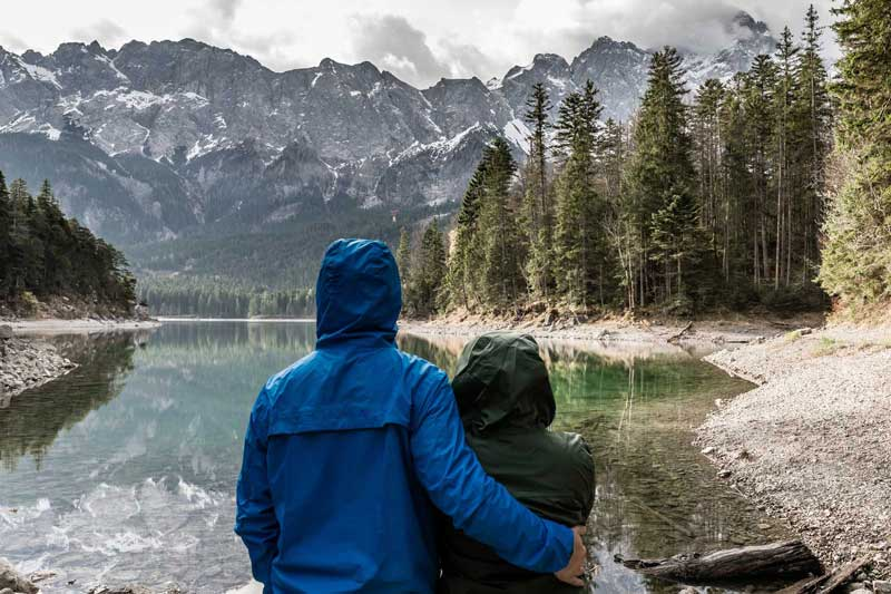 Ultimate guide to hiking clothing -Two hikers with hooded jackets near lake