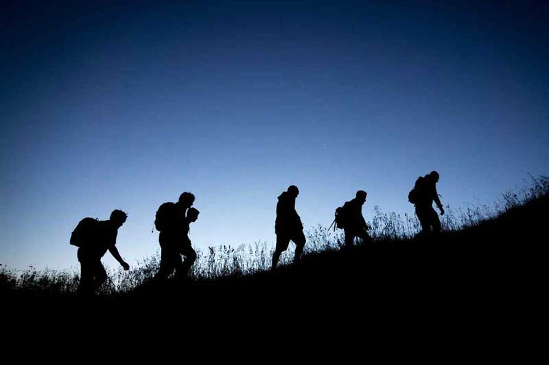Night hiking - a group of hikers walking at night