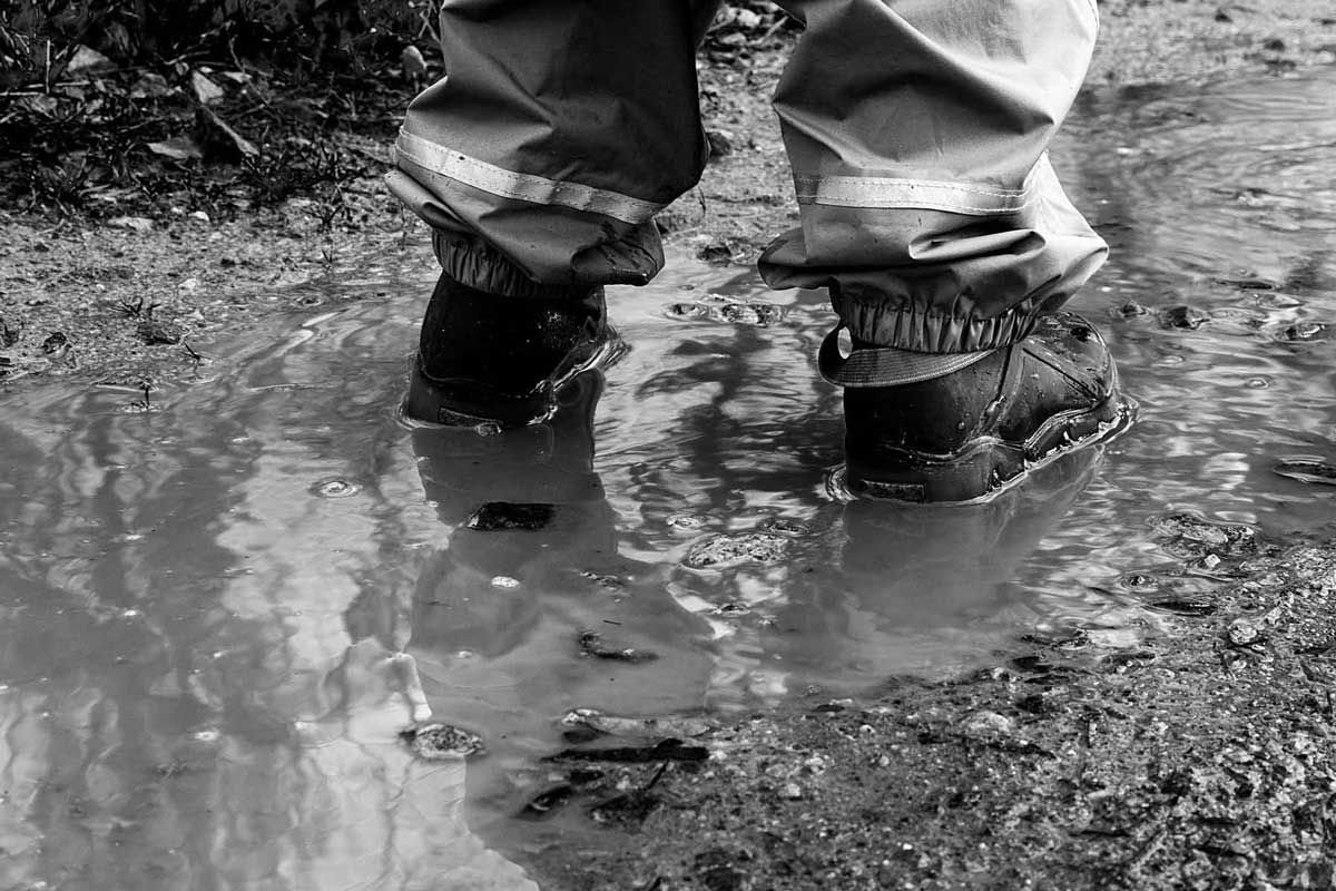 Hiker wearing rain pants walking through puddle