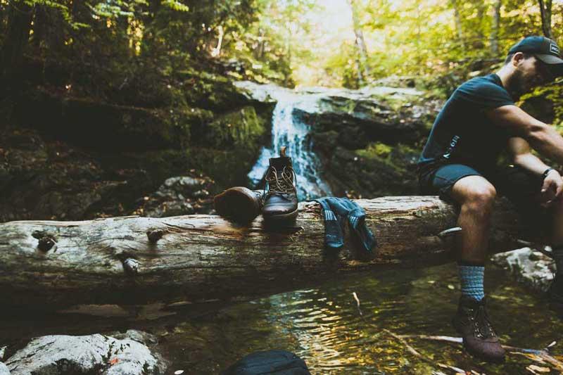Adventurer washing his hiking socks in nature