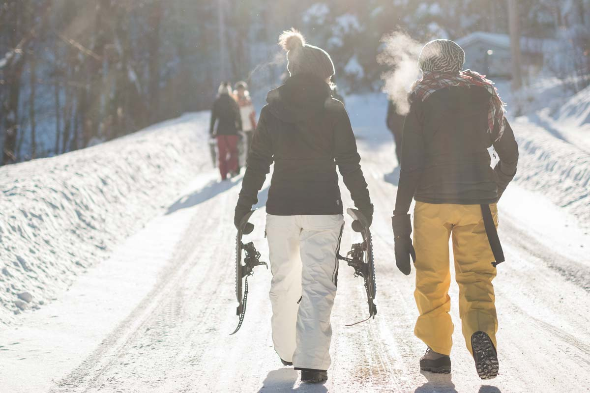 Hikers wearing mittens carry snowshoes
